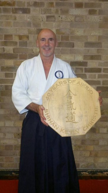 Shihan Kevin Christie with a carved wooden plaque given to him by Nia Aikido students and dan grades for his 40 years in Aikido